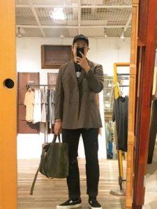ローアンバー系のジャケットとブラックのデニムパンツ