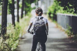 リュックを背負って自転車に乗る女性