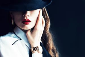 黒い帽子に赤のリップとゴールドの腕時計を身に着けた女性
