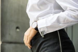白いシャツに黒の腕時計と黒のデニムを履いた女性