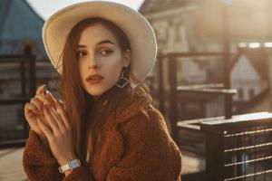 白の帽子にブラウンのアウターを着た時計を身に着けた女性