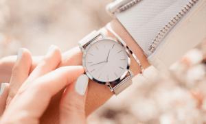 白いジャケットを着た女性が付けているベージュの腕時計のアップ