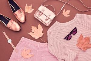 秋が来る。ファッションレディーの服セット。トレンディ・コージー・ジャンパー。スタイリッシュな金色のハンドバッグクラッチ、グラマーサングラス。平らなレイ。秋の葉。バニラパステル秋のおしゃれな色。